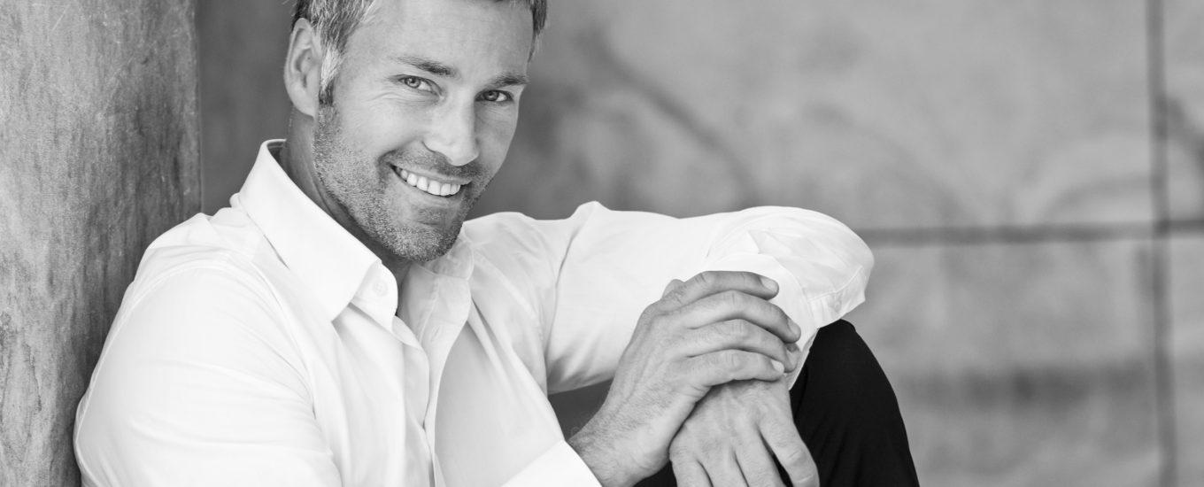 An attractive masculine man with grey hair looking friendly. He is sitting on the ground, leaning with his back at a wall and smiling at the camera. He is wearing a white button down shirt with open collar. The black and white image was shot outdoors. There is some copy space on the top of the right side.